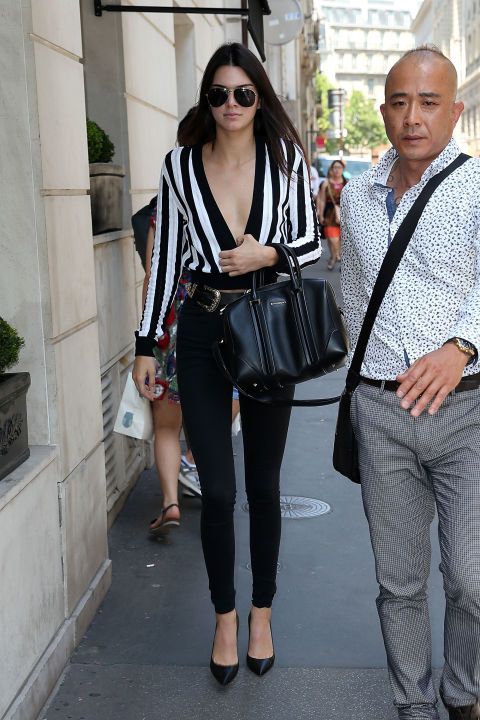 In Paris, she opts for a plunging striped top, high-waisted cigarette pants, a leather belt, and black pumps.