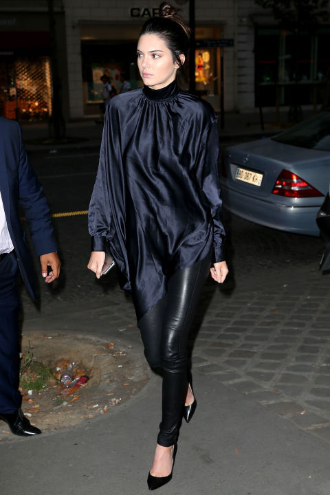 In Paris, she goes the black-on-black route with a silky turtleneck smock top and leather leggings.