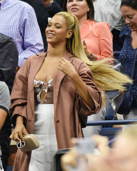 Bey cozied up next to Jay-Z at the U.S. Open wearing a floral corset top with acleavage-bearing cutout paired with a mid-length, ribbed skirt. She layered the look with a dusty pink jacket, seamlessly transitioning into fall fashion.