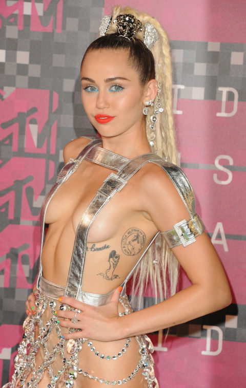 "Miley Cyrus got her first tattoo at 17—script of ""Just Breathe"" below her breast—as a tribute to her friend Vanessa who had died of lung disease and both of her grandfathers, who had died of lung cancer.""It reminds me not to take things for granted. I mean breathing—that was something none of them could do, the most basic thing. And I put it near my heart, because that is where they will always be,"" she told Harper's Bazaar."