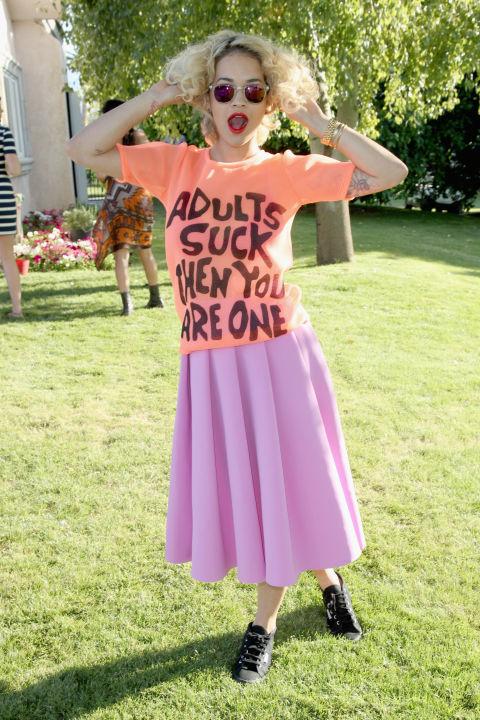 """Se você é da mentalidade """"mais é mais"""", faça como Rita Ora e use um tee gráfico com uma saia midi igualmente brilhante. & Nbsp;"""