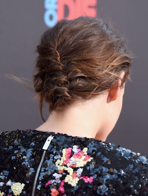 A loose modified French twist (running top to bottom instead of vice versa) makes the most of her air-dried texture.